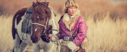 A Mongolian woman holding her horse in a field as the wind blows against her face and the tall grass